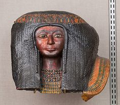 Funerary Mask of a Woman, Egypt, 1479–1425 B.C.  The full, elaborate wig with its ornamental fillet, the necklace of ball beads and pendant nefer signs, and the woman's facial features are similar to the sculpture and painting style of middle of Dynasty 18. The owner was probably the wife of an overseer of builders named Amenhotep.