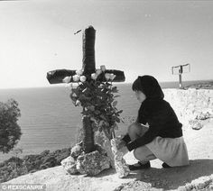 Site of the car crash that killed Princess Grace of Monaco / Grace Kelly, with mourner praying at cross in 1982.