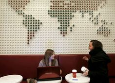 Artwork made of coffee cups is the backdrop for tables at the Starbucks Reserve store in Seattle's University Village.