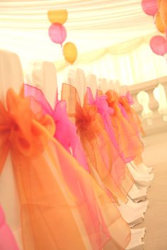 Fuschia pink & tangerine organsa chair bows on white linen chair covers.  Styled by www.fuschiadesigns.co.uk.