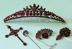 A Collection Of Antique Bohemian Garnet Jewellery Circa 1890 Comprising a tiara, cross, two pendant brooches, target brooch and a stick pin, all encrusted in rose cut garnets, the cross mounted in 9ct rose gold, the rest of the collection mounted in silver gilt.