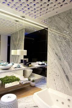Outro destaque está no teto: o elemento vazado cria um efeito interessante de iluminação e esconde o sistema de circulação do ar, já que o espaço não possui janelas.