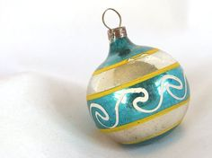 This small, vintage Christmas ornament was mouth blown. The silver ornament has turquoise blue outlined with thin yellow stripes.