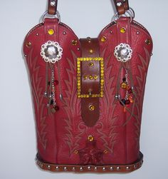 This red vintage leather JUSTIN cowboy boot purse is named RUTHIE. She sports two round silver conchos with hanging purse charms that catch the eye as she moves. She stand upright on a wooden oak base which allows for ample room for carrying all of your personal belongs. She is adorned with topaz and clear crystal gems. Her lining is whimsical calico that continues the western charm inside. She can go out day or night and always be the topic of conversation.
