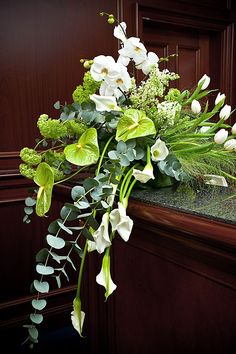 Lime-green anthurium, white phaelonopsis, silver-green eucalyptus, and lorashen make the perfect arrangement for any funeral or memorial service.