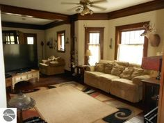 Living room of a home built in 1917 at 123 W. End St. in Alma, Michigan. Asking price $144,900. The 3 story home features 2,912 sq. ft., 6 bedrooms, 2 bathrooms, stone exterior, built-in bookcase, foyer, formal dining room, den/study, fireplace, hardwood floors, beamed ceilings, original woodwork, beveled glass pocket doors, double-decker glass enclosed porches overlooking backyard, large updated kitchen with island, 10 x 16 bonus room on 3rd floor, detached garage and 6,970 sq. ft. lot.