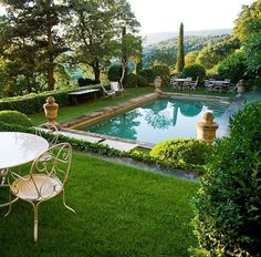 Perfection in a backyard pool - clipped hedges, grass surround, urns on each corner, white iron furniture. I think white umbrellas would be really nice here too