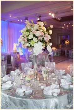 Lovely white & blush floral centerpiece at this blue uplighting wedding!: