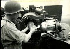 Great close-up of a crewman adding a propellant charge to a 155mm howitzer.