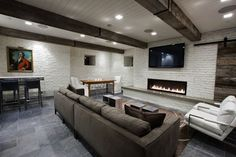 Boutique hotel basement game room with rustic wood beams, white painted exposed brick walls and white wood paneled ceiling with recessed lighting. Flatscreen TV over modern fireplace, salvaged wood sliding barn doors, charcoal gray microfiber sofa, white leather modern chairs and slate tiles floor.