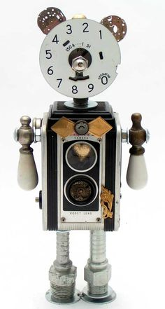 """Smooth Operator""   Height: 12""   Principal Components: Camera, phone dial plate, pressure gauge, faucet handles, watch parts, hose fittings, button  All Fobots have a heart inside--you can see this one by looking through the top lens of the camera!"