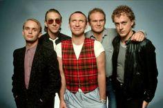 Greg Ham na ponta esquerda, junto com outros integrantes da banda Men at Work