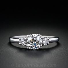 Classic elegance in an original vintage diamond and platinum engagement ring from the 1930s. A sparkling European cut diamond weighing .67 carat is flanked on both sides by a tiny accent diamond. Simple, straight forward and radiant.