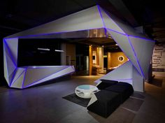 Angular exhibit structure with purple light detail; ABC Emporio by NU.DE