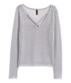 Loose-knit jumper with long sleeves and a V-neck with crossover straps at the neckline.