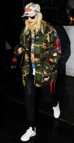 Rita Ora in a patchwork camo jacket, leather leggings, and white sneakers