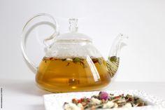 Green tea, flowers and spices tea blend inside a glass teapot