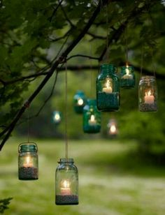 Hanging mason jars with sand and candles for natural outdoor party lighting in the evening