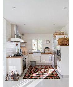 White kitchen w. kelim rug from Danish or Swedish interior design magazine.