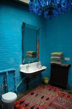 Simple old bathroom, with lovely old sink and carpets, and beautiful blue chandelier.
