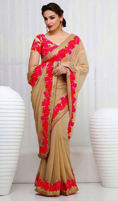 Trendy beige embroidered georgette sari has floral inspired design. The sari is ornamented with woven lace, uniquely silk thread embroidered floral border, sequins and scattered crystal stones which makes you center of attraction of everybody's eyes. The sari comes with matching stitched blouse as shown in the picture. #ReshamWorkDesignerSarees