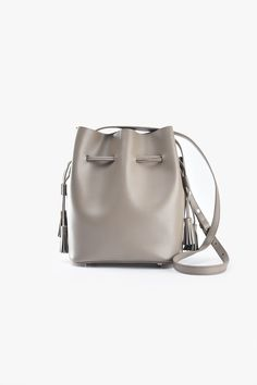 Day-to-night leather bucket bag with drawstring closure, leather tassel detail and adjustable shoulder strap with zip pouch. Size & Fit Length: / Width: / Height: / Strap length: / Extension strap length: / Strap width: / Content &a Leather Tassel, Leather Bag, White Leather, Cheap Handbags, Bucket Bag, Shoulder Strap, Pouch, Mini, Pastel