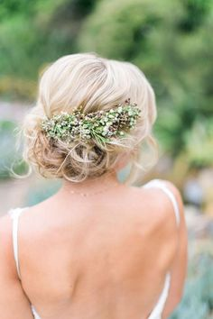 Blonde updo with swath of tiny flowers.