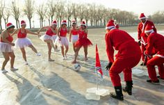 Winter swimmers wearing Santa Claus costumes play soccer on a
