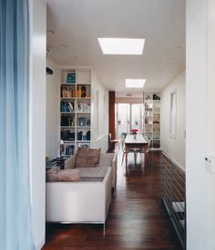 Once a split-level jumble of small, dark rooms, the main floor now offers a clear sight line from the patio straight through the kitchen, dining room, sitting area, and spare room to the street-facing window (with two skylights for added illumination).  Photo by Zubin Shroff.