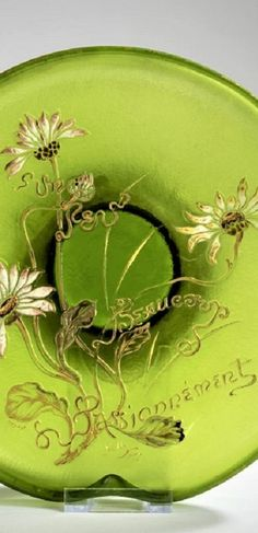 Detail - 'Verrerie parlante'. H. 6.7 cm, D. 23.7 cm. Overlaid glass, colourless and green. Etched and polychrome enamelled decoration with daisies and the counting rhyme: Un Peu Beaucoup Passionnément; heightened with gold. Signed: Déposé Gallé Nancy (gold heightened). Silver mounting stamped: Minerva's head. Counting Rhymes, Bowl, Daisies, Overlays, Detail, Decoration, Glass, Green, Silver