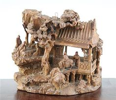 A Chinese hardwood carving of sages, late 19th / early 20th century, the figures depicted in and around a pavilion of rockwork and a pine tree with a mountain stream beneath them, 17.5cm.,