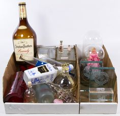 Lot 745: Decorative Glassware Assortment; Including glass and metal display boxes, empty liquor bottles, doll in domed glass display and golf themed paperweights