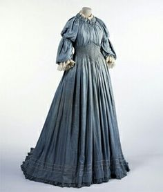 "Liberty and Co. Aesthetic gown c. 1893-1894   Aesthetic Dress: Aesthetic dress of the late 19th century is sometimes also referred to as artistic dress. However, the term ""artistic"" tends to imply this fashion trend was limited only to those in the creative circles. While the fashion movement did get its origins amongst the artists of the period, aesthetic dress did spill over into mainstream fashion. Dresses were typically made of cotton, linen, velvet, wool, or oriental silk. They were…"