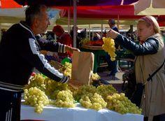 "Grapes change hands at Ljubljana's sprawling farmer's market, considered a ""Green City"" attribute. Photo: Jonathan Tourtellot"