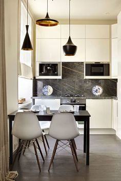 In a Moscow apartment, designer Olga Kulikovskaia-Ashby created a breakfast area within the kitchen. Pendant lights by Tom Dixon hang above the table; the chairs are by Vitra, and the plates on the kitchen counter are by Seletti.