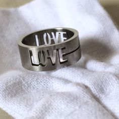 "Stainless Steel ""LOVE"" Ring Very nice, solid ring with ""LOVE"" cut out in the front and back. I believe it is a size 6. Does not tarnish. Great accent piece. Please feel free to make a reasonable offer. No trades. Thanks for looking! Jewelry Rings"