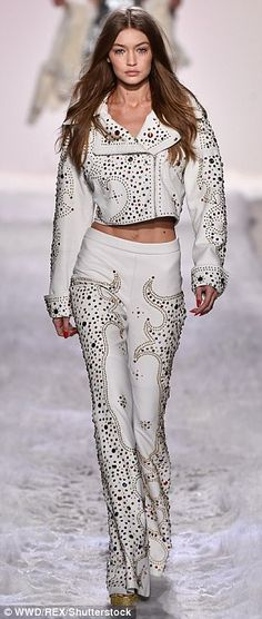 Style star: The 21-year-old Californian beauty showcased her enviable taut stomach as she sashayed down the runway in a daring white leather jacket and pant ensemble