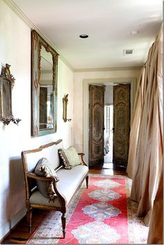 If you can locate some inexpensive, ornate doors at an architectural salvage, you can transform a hallway or bedroom into something awesome. Look at what these doors, curtains, mirrors, and settee did for a standard hallway.