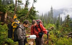 Tired and wet climbers inspect their topo map in Glacier Peak Wilderness, Washington.