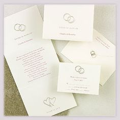 """With this ring wedding invitations A simple message of love is represented on this z-fold invitation featuring two silver foil rings with """"United in Marriage"""" (stamped in silver foil) printed below. Two silver foil hearts are printed below your wording accompanied by the words """"Joined in Love"""" (stamped in silver foil). Please specify bride and groom's names for the front."""