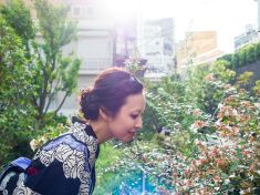 Japanese Young Yukata woman smelling fragrance of flowers at park stock photo