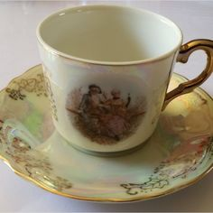 """1920 - 1940' Small """"Courting Couple"""" Cup & Saucer -  Lusterware Dimensions Cup +/- .  78 x 60 x 55 (mm) :  3,07 x 2,36 x 2,17 (inch) Weight Cup +/- .  73 g :  2,57 ounces Dimensions Saucer +/- .  115 x 115 x 18   4,53 x 4,53 x 0,71 (inch) Weight Saucer +/- .  52   1,83 ounces"""