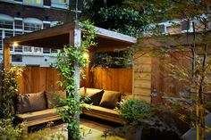 The pergola works hard, and its multiple uses exemplify Boekel's design mantra for the garden. It shelters the outdoor sofa, supports the climbing star jasmine (Trachelospermum jasminoides) and holds the outdoor lighting. Small City Garden, Narrow Garden, Small Garden Design, Small Gardens, Outdoor Seating Areas, Patio Seating, Garden Seating, Garden Table, Patio Pergola