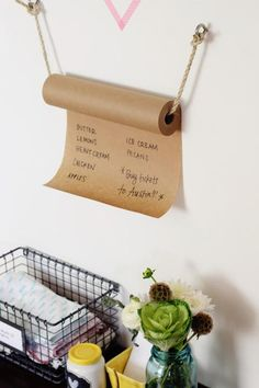 DIY Kraft Paper Grocery List Roll- A cute way to keep your grocery list.  Make a roll hanger using rope.