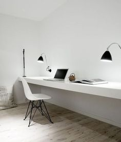 Office space for the minimalist. White desk and chair, light hardwood floor…
