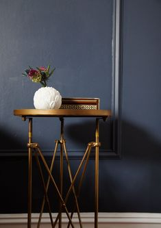 An accordion-style brass side table topped with feminine details