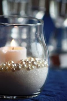 This is an elegant, neutral centerpiece solution. Put fake pearls (available at most craft stores), local sand, and a candle in the votive together for table ambiance.