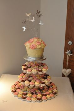 Pastel pink and cream wedding cupcakes with giant rose cupcake and wire butterfly topper by Little Miss Cupcakes