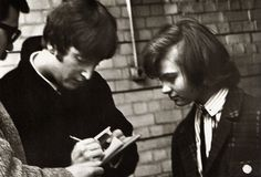 "May 1964. John signs an autograph for a fan during rehearsals for ""Around The Beatles"" at Wembley."