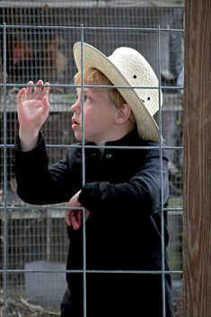 This young Amish boy stands watching the comings and goings of birds being auctioned at a semi-annual fundraiser for an Amish one room school located in central Pennsylvania.